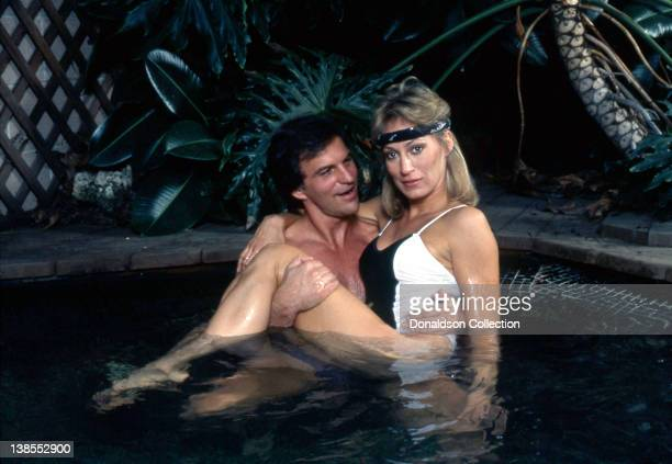 Celebrity couple Josh Taylor and Sandahl Bergman pose for a portrait in the jacuzzi at their home in circa 1985 in Los Angeles California