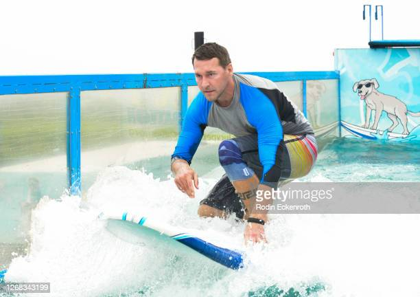 Celebrity Dog Trainer Brandon McMillan demonstrates his surfing skills on The Lucy Pet Foundation Dog Wave Truck today while taping a segment for...