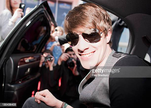 celebrity emerging from car towards paparazzi - celebrities stock pictures, royalty-free photos & images