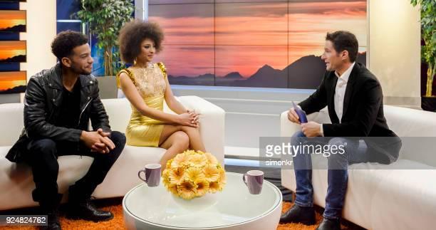 vip-gasten in talkshow praten met mannelijke host en publiek - gast stockfoto's en -beelden