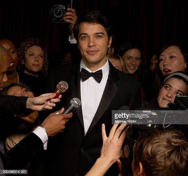 celebrity male in tuxedo talking to fans and media at event, portrait - red carpet event photos et images de collection