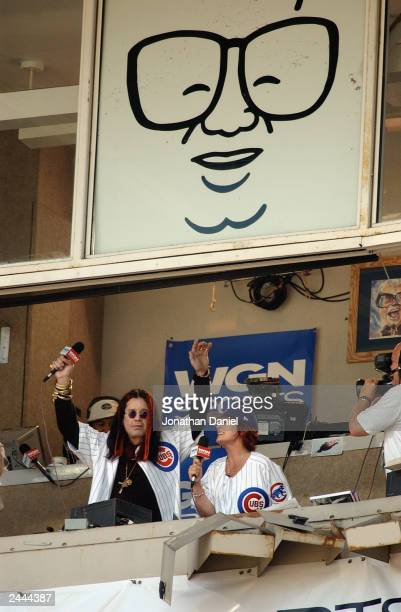 Celebrity Ozzy Osbourne and his wife Sharon sing 'Take Me Out to the Ball Game' during the seventh inning stretch of the National League game between...
