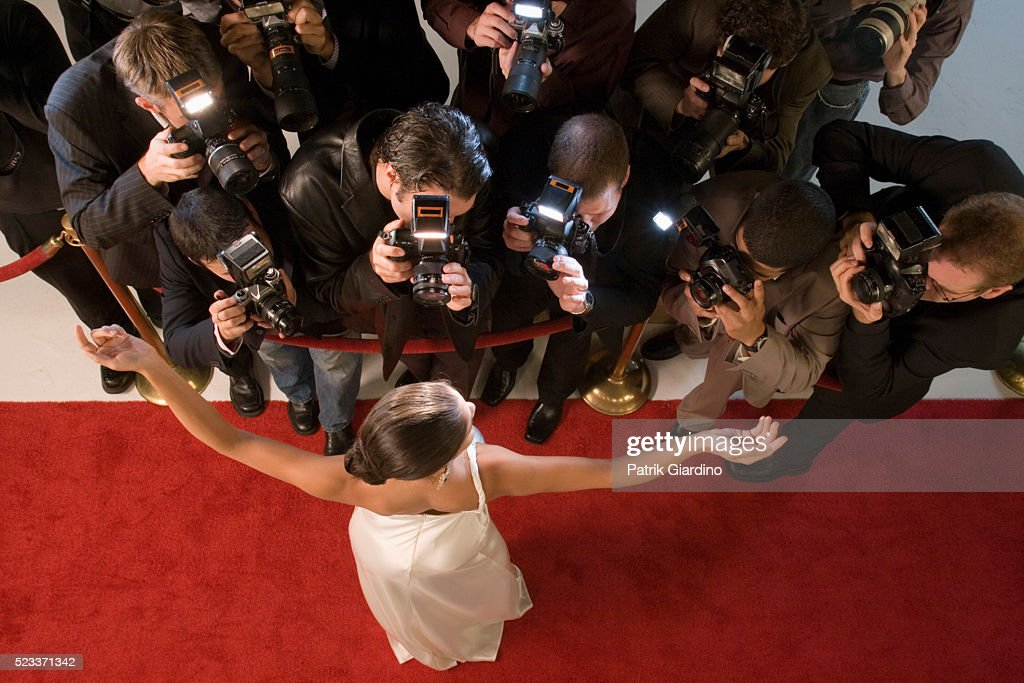 Celebrity Posing For Paparazzi At Red Carpet Event Stock Photo