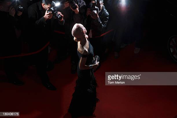 celebrity posing for paparazzi on red carpet - evening gown stock pictures, royalty-free photos & images