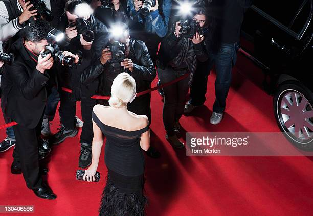 celebrity posing for paparazzi on red carpet - beroemdheden stockfoto's en -beelden