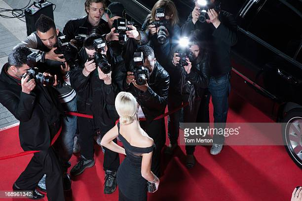 celebrity posing for paparazzi on red carpet - actor stockfoto's en -beelden