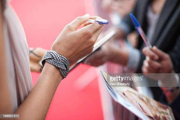 Celebrity signing autographs for fan