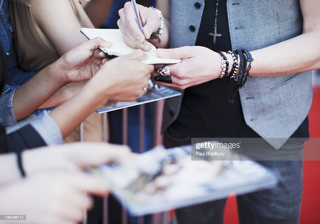 Celebrity signing autographs on red carpet : Stock Photo