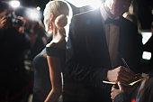Celebrity signing autographs on red carpet