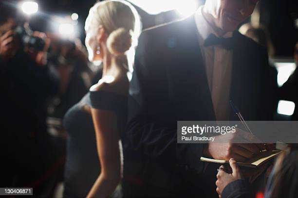 celebrity signing autographs on red carpet - evening gown stock photos and pictures