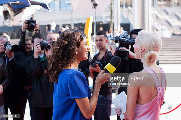 Celebrity speaking to reporters on red carpet