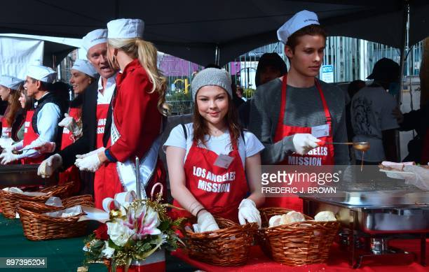 Celebrity volunteers Hannah Zeile and Logan Shroyer join volunteers at the Los Angeles Mission's annual Christmas meal for the homeless on December...