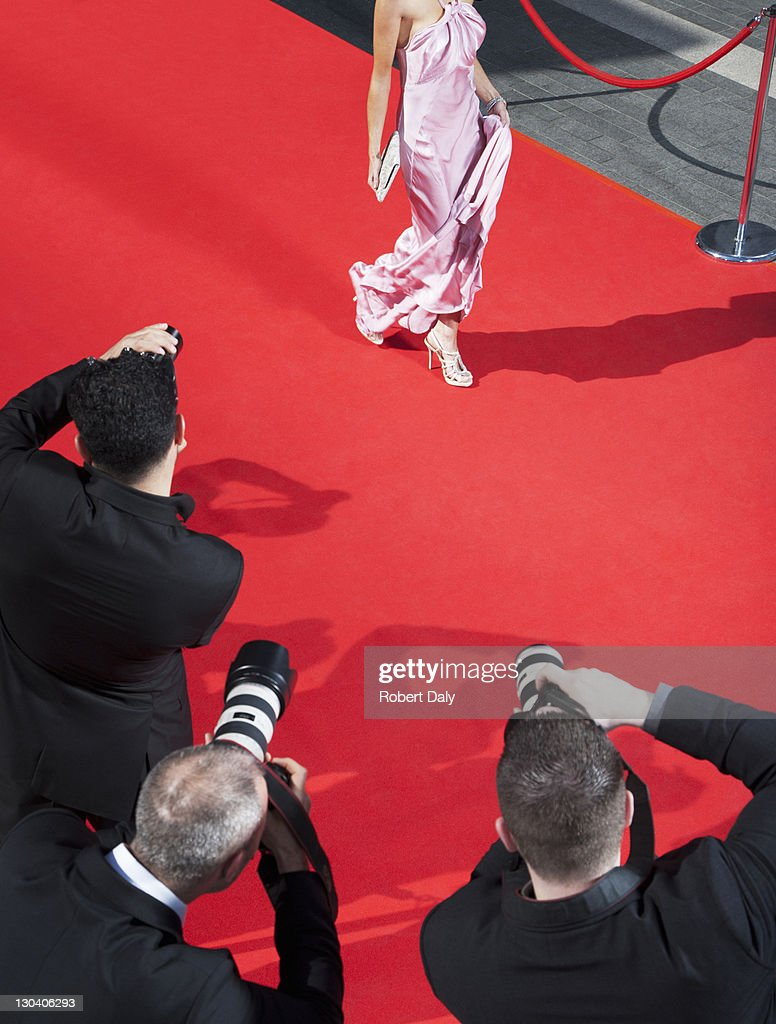 Celebrity walking for paparazzi on red carpet : Stock Photo
