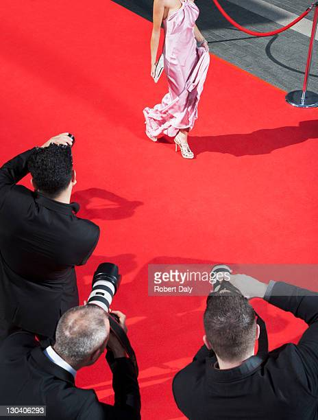 Celebrity walking for paparazzi on red carpet