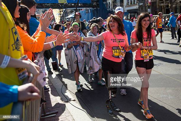 Celeste Corcoran gives high fives while she is helped by her daughter Sydney Corcoran after finishing the Boston Marathon on April 21 2014 in Boston...