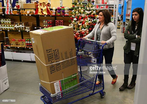 Celeste Corcoran wheels out a Christmas tree in a box with her daughter Sydney from a Lowes store that was purchased for their dining room window...