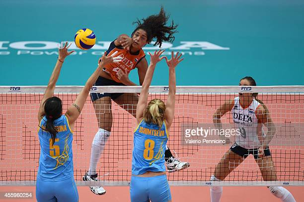 Celeste Plak of Netherlands smashes as Olga Nassedidkina and Korinna Ishimtseva of Kazakhstan block during the FIVB Women's World Championship pool C...