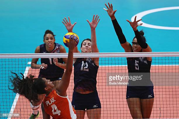 Celeste Plak of Netherlands spikes the ball against Kelly Murphy and Rachael Adams of United States during the Women's Bronze Medal Match between...