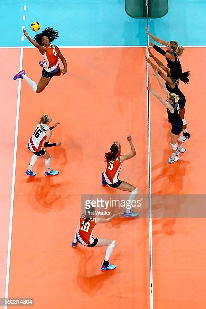 Celeste Plak of Netherlands spikes the ball against Kimberly Hill Foluke Akinradewo and Karsta Lowe of United States during the Women's Bronze Medal...