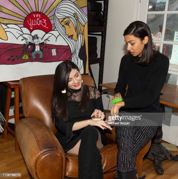 Celeste Thorson and Lilly Lawerence using QYKsonic skincare device at The Wild Immersion Los Angeles Premiere At TAP on January 31 2019 in Los...