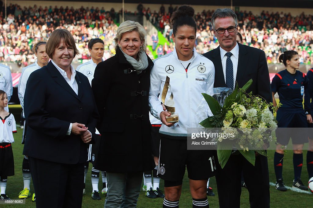 Celia Sasic poses with head coach Silvia Neid, DFB General Secretary Helmut Sandrock and DFB Vice President Hannelore Ratzeburg during the Women's International Friendly match between Germany and Brazil at Trolli-Arena on April 8, 2015 in Fuerth, Germany.