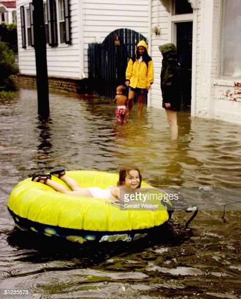 Celia Smith enjoys a ride on an inflatable tube while floating along a flooded street August 29, 2004 in downtown Charleston, South Carolina. The...