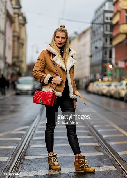 Celina Ruf with bun hair wearing a beige sheepskin jacket red Chanel bag black leggings net tights beige Isabel Marant Atoile fed winter boots with...