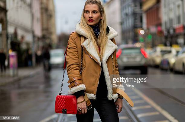 Celina Ruf with bun hair wearing a beige sheepskin jacket red Chanel bag black leggings net tights on December 28 2016 in Berlin Germany