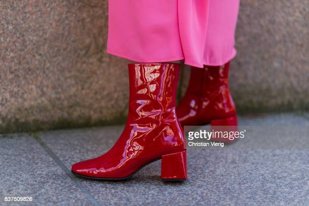 Celine Aagaard wearing a pink dress red clutch and red boots outside IBEN on August 22 2017 in Oslo Norway