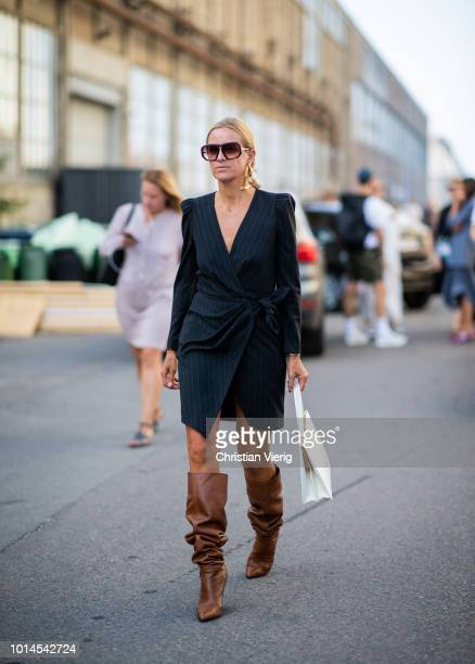 Celine Aagaard wearing black striped dress brown leather boots seen outside Ganni during the Copenhagen Fashion Week Spring/Summer 2019 on August 9...