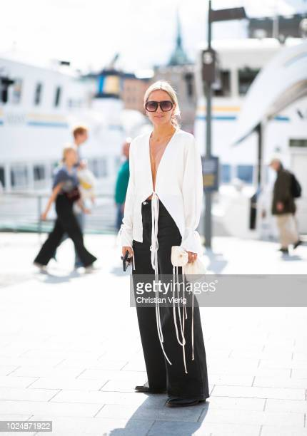 Celine Aagaard wearing black wide leg pants, white blouse with fringes, mini bag is seen during Stockholm Runway SS19 on August 28, 2018 in...