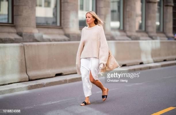 Celine Aagaard wearing white silk dress, knit, sandals seen outside Epilogue during Oslo Runway SS19 on August 14, 2018 in Oslo, Norway.