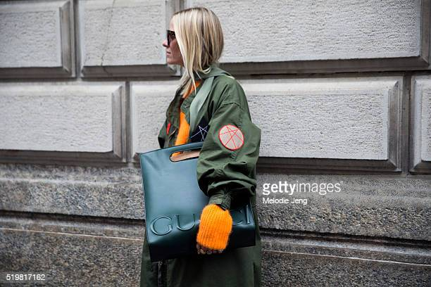 Celine Aagaard wears Celine sunglasses a long green Whyred armystyle coat with patches an orange knit sweater and a W16 green Gucci XL leather tot...