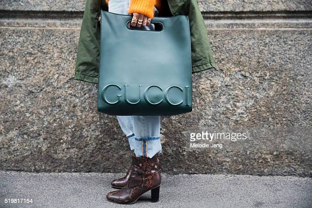 Celine Aagaard wears rings and carries a FW16 green Gucci XL leather tote over uffed jeans and python print brown boots outside the Sportmax show...