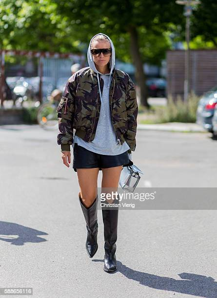 Celine Aargaard wearing a camouflage military bomber jacket grey hoody and black boots outside Ganni during the second day of the Copenhagen Fashion...