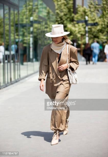 Celine Aargaard wearing brown jacket, pants, hat, scarf, creme white bag outside Kenzo during Paris Fashion Week - Menswear Spring/Summer 2020 on...