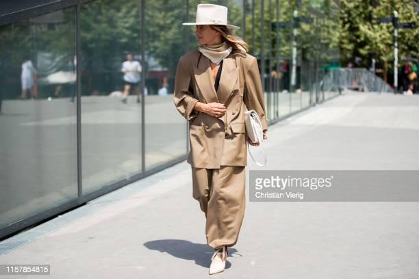 Celine Aargaard wearing brown jacket pants hat scarf creme white bag outside Kenzo during Paris Fashion Week Menswear Spring/Summer 2020 on June 23...
