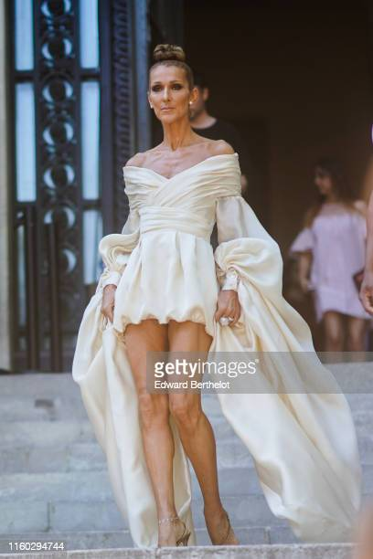 Celine Dion wears earrings, rings, a lustrous ivory-color off-shoulder drape mini dress with long flowing puff sleeves, anklets, shiny golden strappy...