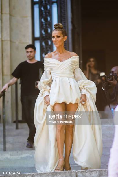 Celine Dion wears earrings rings a lustrous ivorycolor offshoulder drape mini dress with long flowing puff sleeves anklets shiny golden strappy...