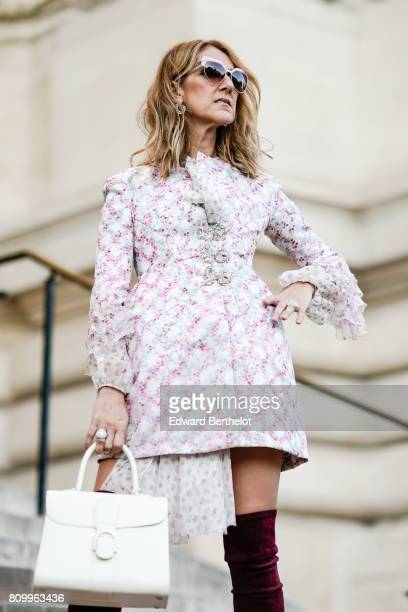 Celine Dion wears sunglasses a dress with embroidered features and lace a white bag and purple thigh high velvet boots outside the Giambattista Valli...