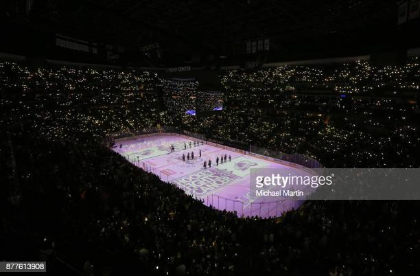 Cell phone lights illuminate the stands during a moment of silence for Hockey Fights Cancer prior to the game between the Colorado Avalanche and the...