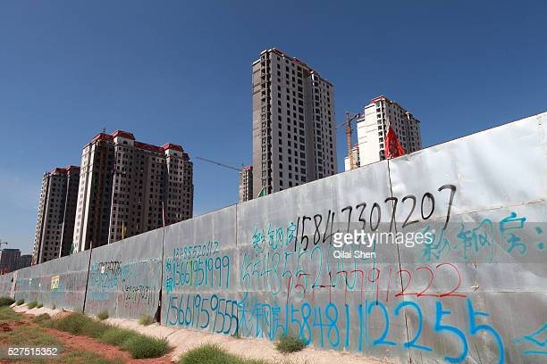 Cell phone numbers advertising construction equipment and material rental decorate a wall surrounding a densely built residential apartment...