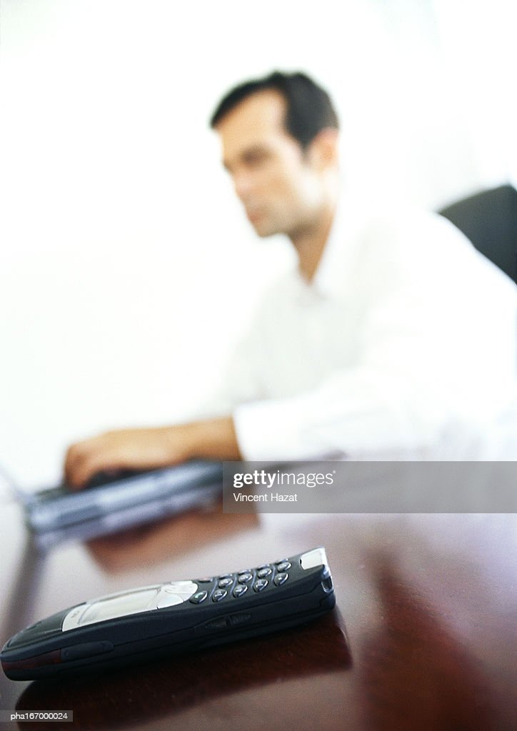Cell phone on businessman's desk, blurred background : Stockfoto