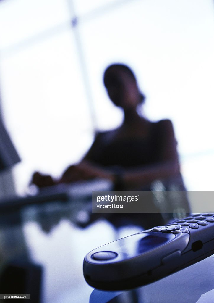 Cell phone on businesswoman's desk, close-up : Stockfoto
