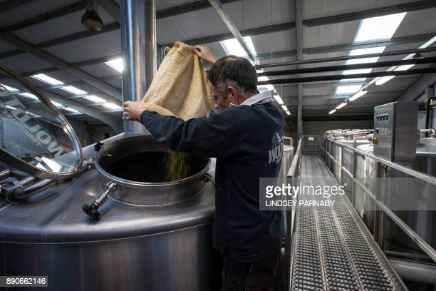 Cellarman and Brewer Tony O'RourkeKilburn adds barley to the kettle during the process of brewing Toast Ale from stale bread barley and hops at the...