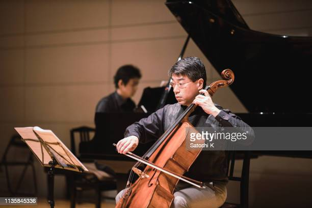 cellist and pianist playing in classical music concert - classical concert stock pictures, royalty-free photos & images