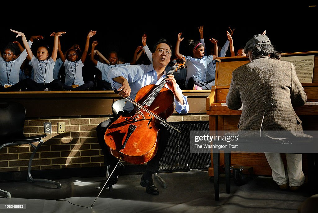 Cellist Yo Yo Ma and dancer Damian Woetzel hold a music and dance workshop with kids at Savoy Elementary in Washington, DC. : News Photo