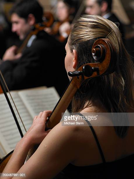 Cellists performing in orchestra, focus on woman in foreground