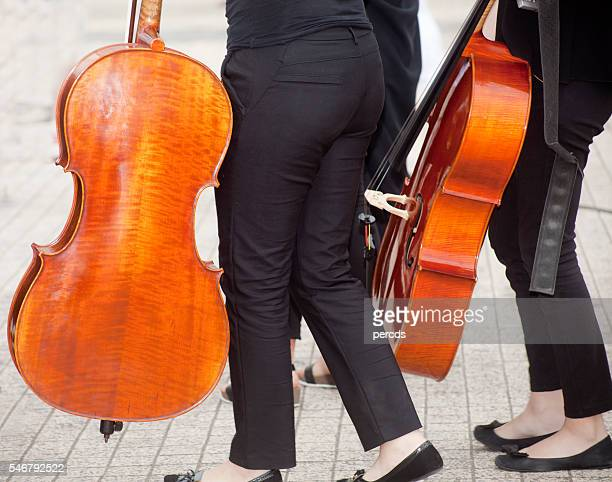 Cellists walking with cellos.