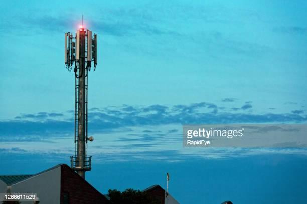 la stazione base del cellulare sovrasta i tetti delle fabbriche contro un lunatico cielo all'alba - 5g foto e immagini stock